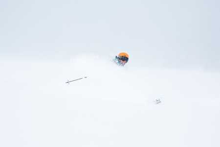 In the Backcountry of Hokkaido, outside Niseko Mountain, a woman skis soft, powdery snow so deep it flies over her head in each turn. She wears a huge smile as she enjoys the snow.