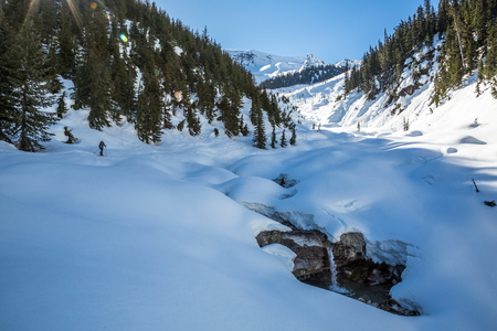 Skier hiking up the Asulkan Valley toward the glacier in the distance. a waterfall on his right has melted out of the spring snow. Stock Photo