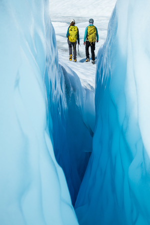 Two ice climbers walking away from a narrow crevasse. The women are ice climbing guides on the Matanuska Glacier in Alaska.