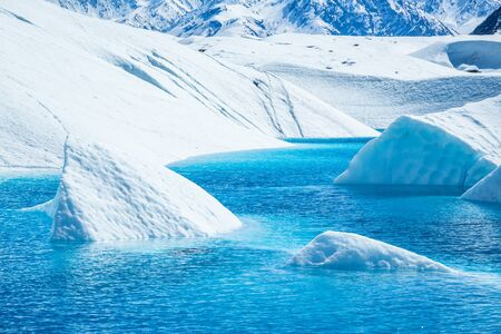 Ice cut from the melting glacier sticking out of crystal blue water on the Matanuska Glacier. Stock Photo