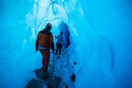 Young man and woman on a guided trek looking into a large tunnel of an ice cave on a glacier in Alaska