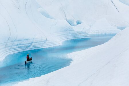 A man paddles solo on an inflatable canoe down a still water river on the Matanuska Glacier in the Alaskan wilderness.