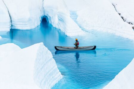 Man paddles a canoe in front of a small flooded ice cave on a glacier lake in the Alaskan wilderness.