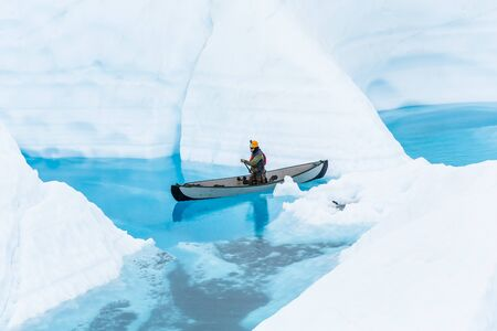 A young ice climber navigates his inflatable canoe through narrow canyons flooded by spring melting of the Matanuska Glacier.