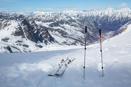 After a long hike, skis and poles sit near the top, overlooking a vast glacial valley below Snowbird Glacier in the Hatcher Pass area of the Talkeetna Mountains, Alaska.