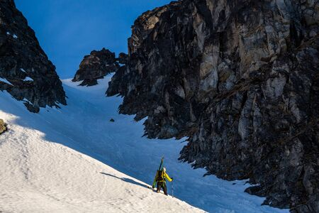 Backcountry skiing in Alaska, a skier hikes up a steep chute or couloir with his skis strapped to his pack. Hiking up steep slope to ski the backcountry in the Talkeetna Mountains.