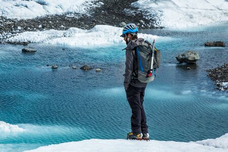 Young man standing with hands in pockets looking out over a blue pool on top of the white ice of the Matanuska Glacier in Alaska. Stock Photo
