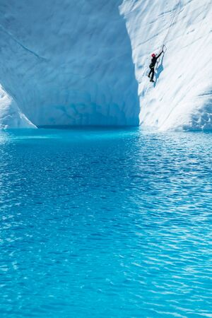 Woman ice climbing above the deep blue water of a glacier lake on the Matanuska Glacier in Alaska.