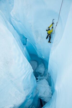Man following the leader of a steep ice climb out of an overhanging wall of a moulin on the Matanuska Glacier in Alaska. Stok Fotoğraf