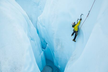 Ice climbing a steep line out of a large hole on glacier ice in Alaska.