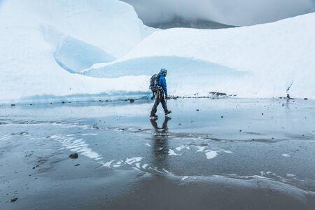 Man walking across flat muddy section of glacier ice on the Matanuska Glacier in Alaska. Stock Photo