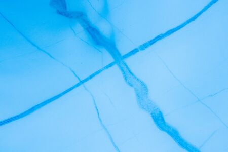 Detail of dark blue cracks through lighter glacier ice. The cracks are refrozen water ice in crevasses or cracks in the ice.