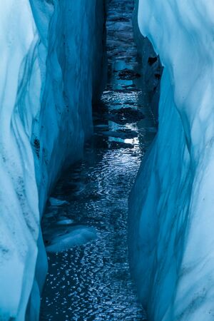 Reflection of the sky looking down inside a large water-filled crevasse on the Matanuska Glacier in Alaska.