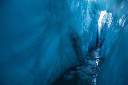 A thin ice bridge spanning a water-filled crevasse. Looking up at hte bright sunlight from deep within a dark crevasse on the Matanuska Glacier.
