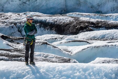 A glacier guide stands observing others on the Matanuska Glacier. His arms are crossed as he waits patiently. Banco de Imagens