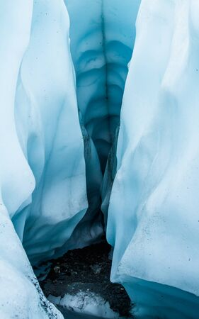 Narrow canyon-like entrance looking into a large ice cave on the Matanuska Glacier in Alaska. Stock Photo