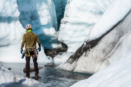 Ice climbing guide passing through a canyon full of shallow water leading to an entrance of an ice cave on the Matanuska Glacier in Alaska.