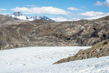 Ghiacciaio in fusione che rivela il substrato roccioso stratificato al di sotto di un remoto picco canadese.