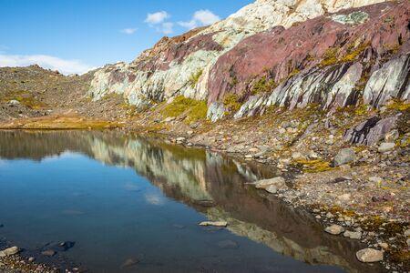 Scogliere rocciose a strati rosse, viola e bianche riflesse nell'acqua limpida di un laghetto calmo sotto il cielo blu. Infiltrazioni di sorgenti e muschio ricoprono le rocce. Archivio Fotografico