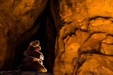 Cairn in dark tunnel through red sandstone slickrock in Moab Utah. Near Arches, Canyonlands, Bryce, Zion, Capital Reef National Parks. Stock Photo