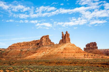 Sun spills through the clouds to light up red rock towers in the Southern Utah Desert.
