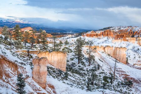 Red and pink cliffs and orange hoodoo towers in southern Utah desert under fresh snow in winter scene. 免版税图像