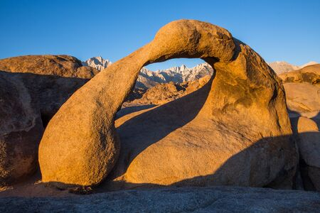 Sunrise over the Eastern Sierra Mountains and Mobius Arch in the Alabama Hills.