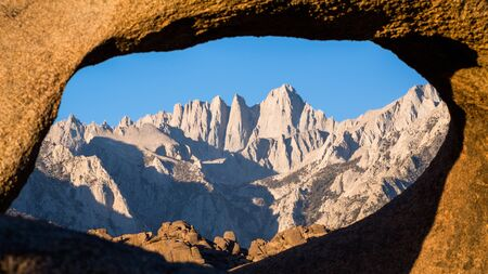 View of Mount Whitney and the Mountaineers route looking through a sandstone archway in the desert near Bishop, California.