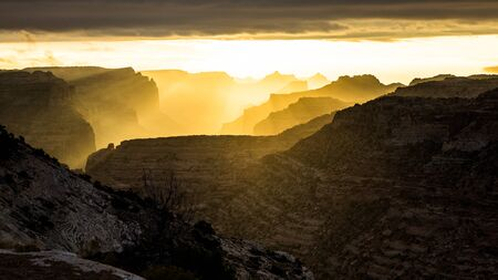 Sunrise in the Utah desert lighting up layers of rocky cliff mesas, buttes and towers backlit by the morning light. Фото со стока