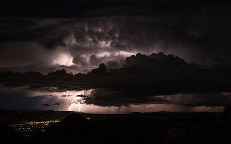 Rainstorm brings flash floods and lightning to the Utah desert near Moab. Distant Lightning strikes illuminate the night and massive thunderclouds over the small town. Фото со стока