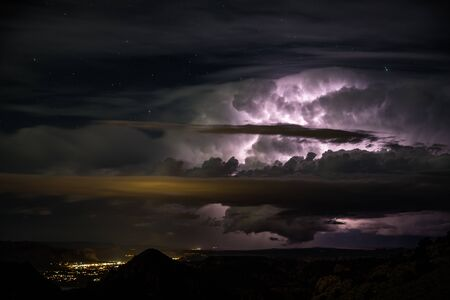 Large evening thunderstorm over small desert town of Moab Utah. Cloud to cloud lightning illuminates the dark night sky with stars visible above the thundercloud. Фото со стока