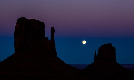 Full moon rising between silhouettes of the iconic mitten formations of Monument Valley after dark.