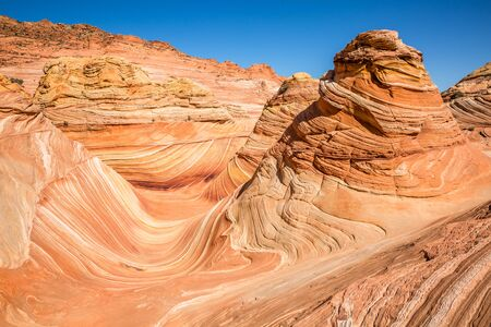 Large cones reminiscent of an orange cream dessert in the Arizona desert above the famous feature, The Wave.