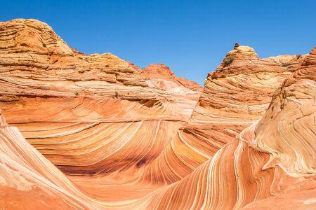Wanderer oder Kletterer sitzen auf dem Gipfel einer Sandsteinkuppel über The Wave of North Coyote Buttes auf der Kaibab Platteau von Arizona.
