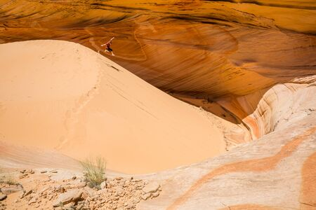 Young man leaps down soft sand dune in the desert of Arizona or Utah with large cliff face behind him.