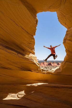 Man in red and brown, hiker jumping for joy in the window of an arch in the desert of Utah or Arizona.