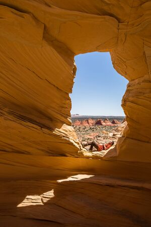 Young hiker stopping to rest or sleep in the sun beneath and archway in the Arizona desert of Coyote Buttes North wilderness.