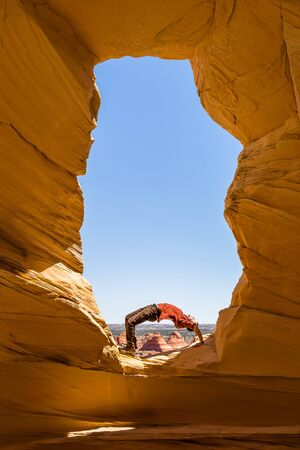 Yoga in wild places, a young man does a back bend inside an arch overlooking the Arizona nad Utah desert on the Kaibab Plateau.