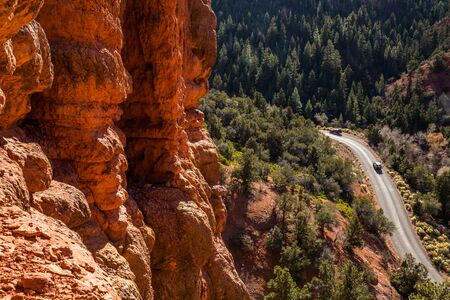 Looking down from red rock towers at narrow canyon road with two trucks driving up the small canyon in Southern Utah wilderness.