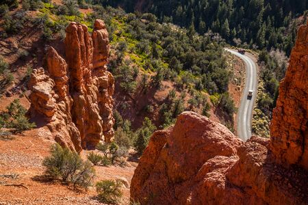 Vehicles on canyon road in Southern Utah. Near Bryce Canyon and Cedar Breaks, the rock looks similar to the hoodoo formations of the National park and Monument