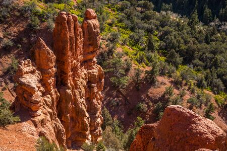 Summer in Brian Head with red rock towers and pine trees in nearby canyon.