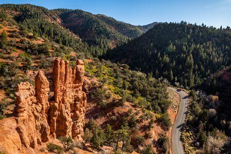 Side road in Parowan Canyon near Brian Head resort in summer. Red rock hoodoos towering over narrow road below.