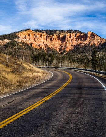 Above the highway leading to Cedar Breaks National Monument stands red rock hoodoo towers and cliffs or pink and orange sandstone.