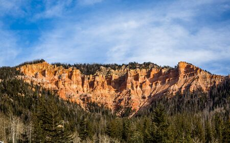 Red rock towers and hoodoos of Southern Utah's Bryce Canyon or Cedar Breaks above green forest in early winter. Blue skies with whispy clouds overhead.
