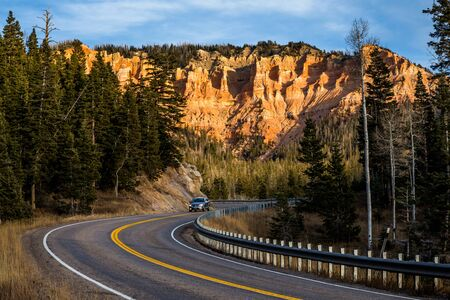 A winding road with silver minivan or SUV driving at sunset, below massive cliffs of red rocks and towers of sandstone in the Utah desert.