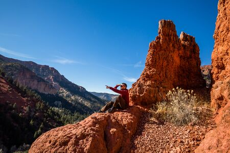 A male hiker sits atop a red rock formation reminiscent of Bryce Canyon National Park. He points off in the distance at something.
