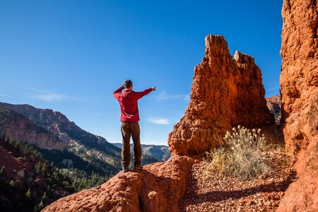 Man in a ared jacket among red rock hoodoo formations pointing at the view down canyon in the Utah desert.