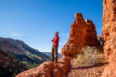 Athletic man standing stoic with crossed arms among the red rock formations of Southern Utah.
