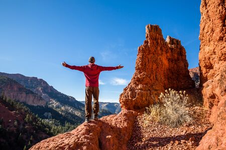 Hiker standing atop red rock formation with arms wide welcoming the view of the Southern Utah desert. Фото со стока