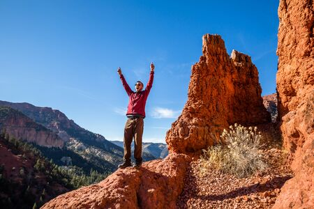 Man excited about climbing to the top of a cliff with a view. Pointing up and yelling in excitement. Фото со стока